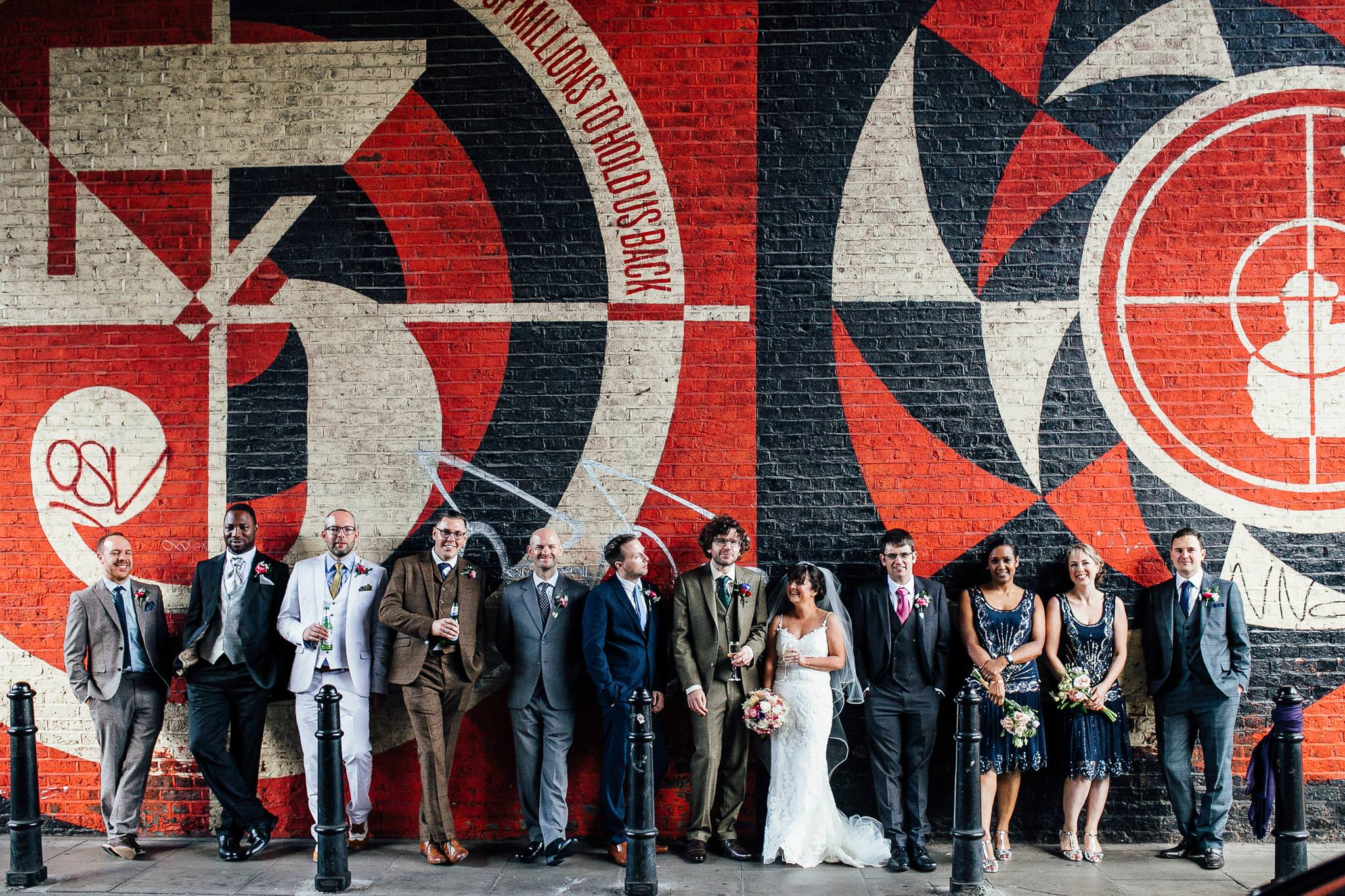 shoreditch studios wedding photos bridal party in front of graffiti wall
